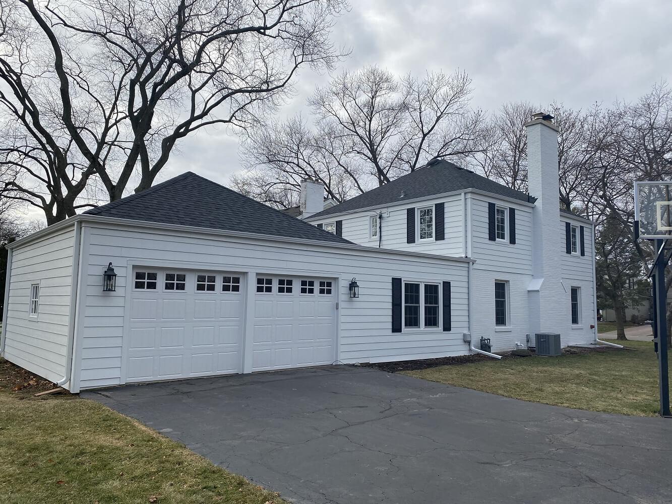 New siding, entry door, roof, and garage doors